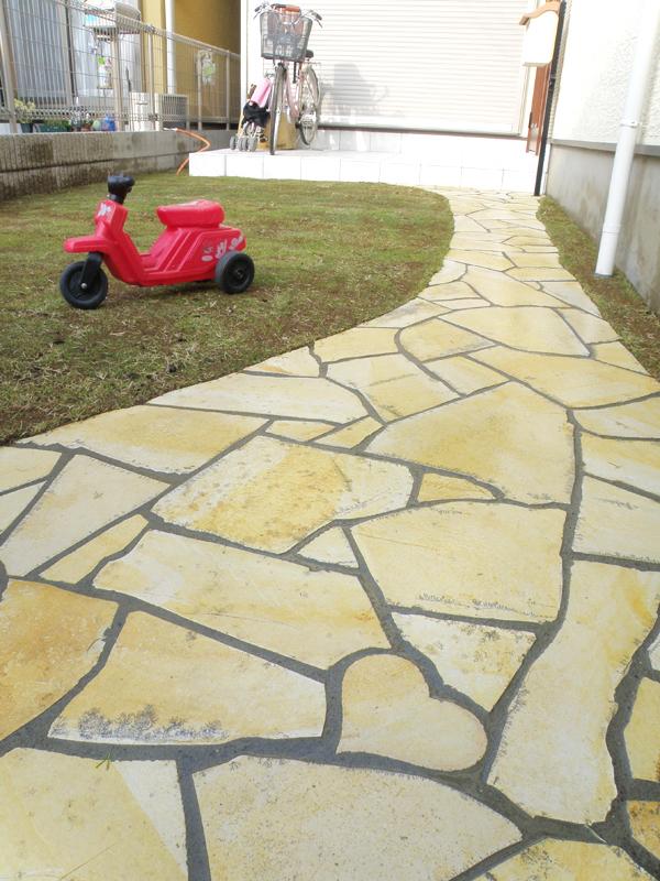 道路から玄関ポーチまでを繋ぐプローチにアーチを描き映える石貼りです。