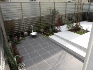 白とグレーのタイルが印象的なシンプルモダンな中庭です。