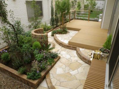 何もなかった中庭にウッドデッキ・花壇・立水栓・黄色い石貼りのアプローチができました。
