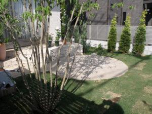 中庭… 植栽と芝生の中にサークルテラスと少し高さのあるステップを兼ねたテラス