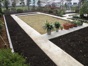 中庭の半分は、コンクリート通路で仕切られた花壇と芝生の庭に…