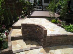 庭は、人工木材ウッドデッキ & レンガと天然石乱貼りテラスを…
