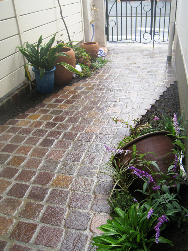アプローチは、方形の天然石を使った石畳風… 味のある色合い