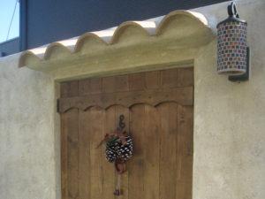 木製の扉の上には洋瓦の屋根、そして こだわりのライトを…