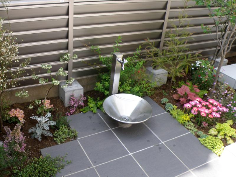 草花に囲まれた立水栓は、金属製でモダンなデザインのものを…