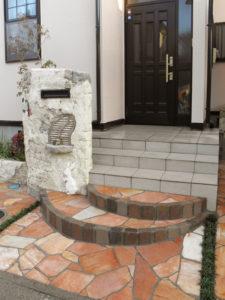 意外と高さのある玄関前の階段を、レンガと天然石乱貼りでデザインしました