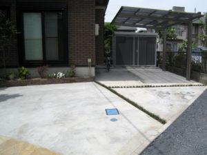 コンクリート打ちの駐車スペースと1台用カーポート、その奥には物置を設置
