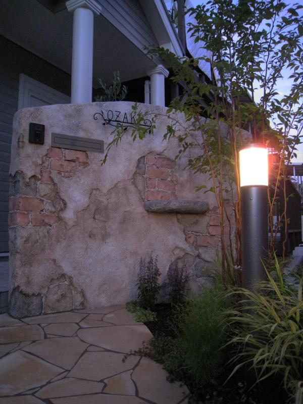 暗闇の中、ライトに照らされたモルタル造形の門袖