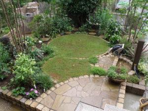 ピンコロをデザイン的に使い、芝生を中心に木々草花に囲まれた庭に…