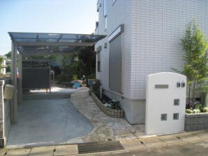 駐車スペース脇のアプローチ&花壇、ポストなど取り付けた白い袖壁…